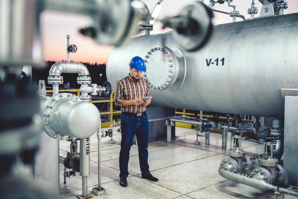 Homem utilizando aplicativo de manutenção na fábrica
